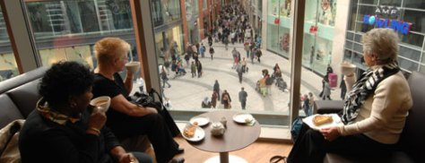 Eden_ladies-drinking-coffee-and-looking-out-of-window-at-busy-shopping-streets